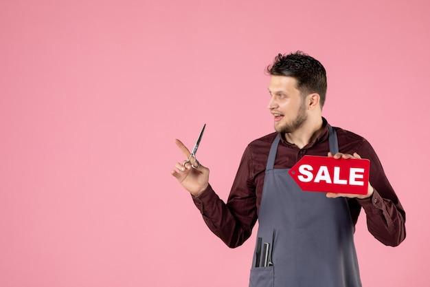 Vorderansicht männlicher friseur mit verkaufstypenschild und schere auf rosa hintergrund