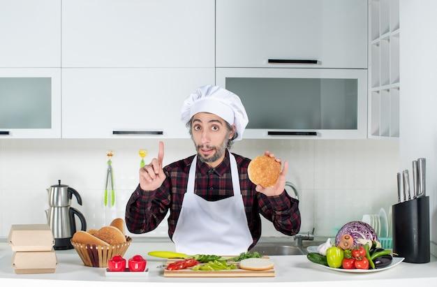 Vorderansicht männlicher koch hält burgerbrot in der küche hoch
