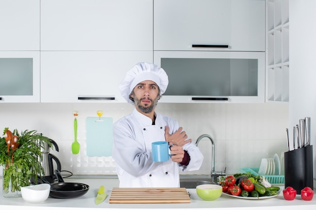 Vorderansicht männlicher koch in kochmütze mit tasse hinter küchentisch