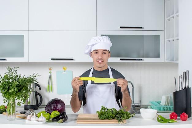 Vorderansicht männlicher koch in uniform mit messer in moderner küche