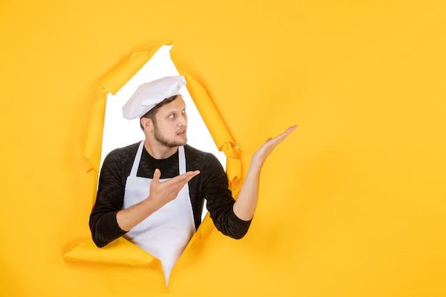 Vorderansicht männlicher koch in weißem umhang und mütze auf dem gelben zerrissenen job-farbfoto-küchen-essen-mann-küche
