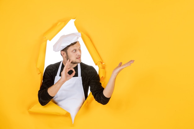 Vorderansicht männlicher koch in weißem umhang und mütze auf gelb zerrissenem job farbfoto küche essen küche