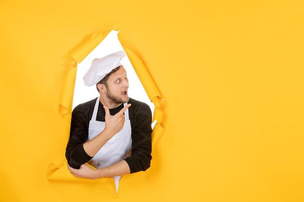 Vorderansicht männlicher koch in weißem umhang und mütze auf gelb zerrissener küche farbfoto küche essen mann