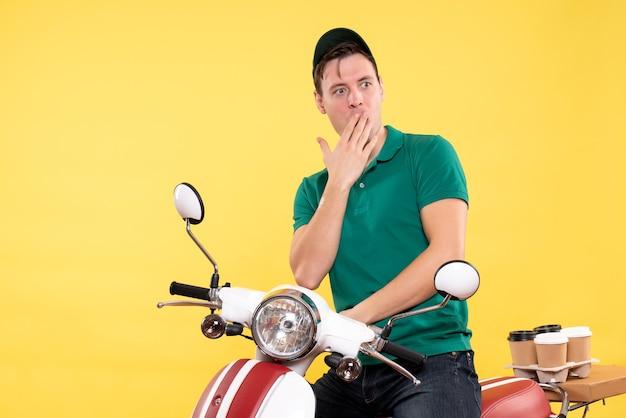 Vorderansicht männlicher kurier auf fahrrad überrascht gelb