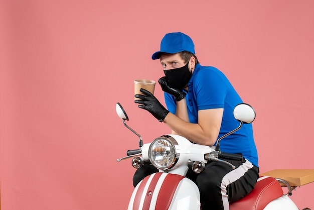 Vorderansicht männlicher kurier, der auf dem fahrrad sitzt und eine große kaffeetasse auf dem rosa hält