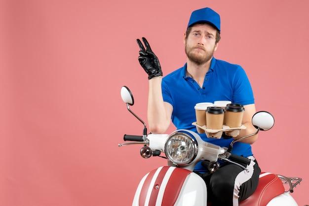 Vorderansicht männlicher kurier, der auf dem fahrrad sitzt und kaffeetassen auf dem rosa hält