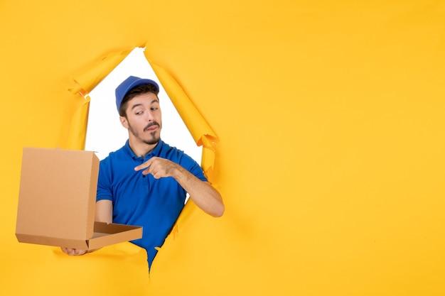 Vorderansicht männlicher kurier, der geöffnete pizzaschachtel auf gelbem raum hält