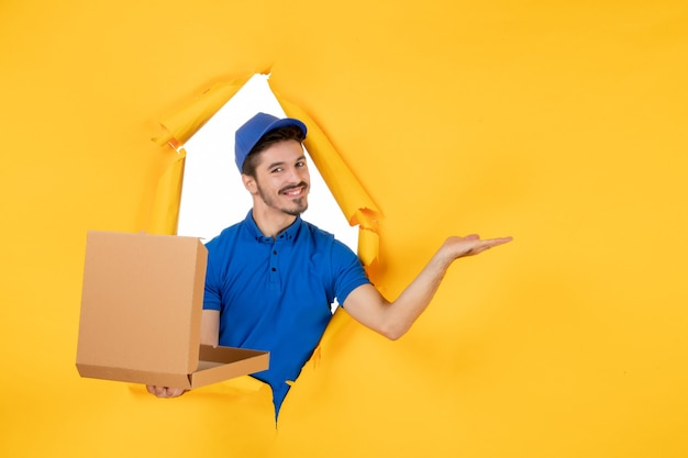 Vorderansicht männlicher kurier, der geöffnete pizzaschachtel hält und auf gelbem raum lächelt