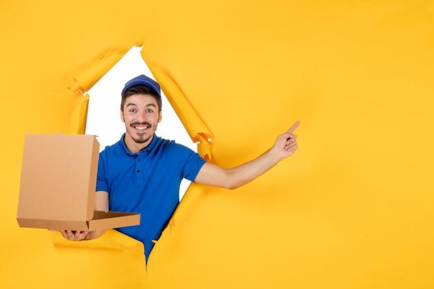Vorderansicht männlicher kurier, der pizzakarton auf gelbem raum öffnet