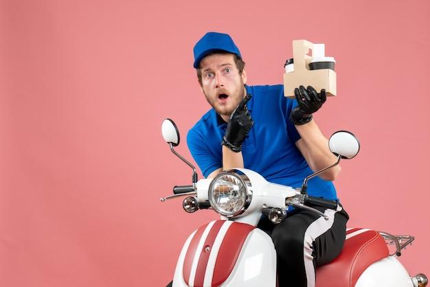 Vorderansicht männlicher kurier in blauer uniform, der auf dem fahrrad sitzt und kaffee auf dem rosa hält