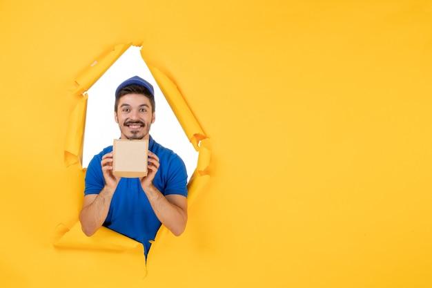 Vorderansicht männlicher kurier in blauer uniform, der ein kleines lebensmittelpaket auf gelbem raum hält
