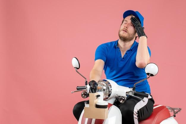 Vorderansicht männlicher kurier in blauer uniform, der kaffee auf dem rosa job hält, fast-food-lieferservice für fahrradservice-arbeiter in farbe