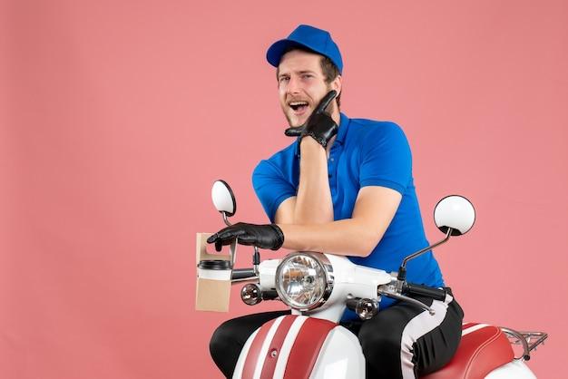 Vorderansicht männlicher kurier in blauer uniform, der kaffee auf rosa job hält fast-food-lieferservice für fahrradservice farbarbeit