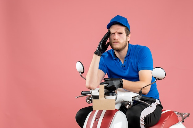 Vorderansicht männlicher kurier in blauer uniform, der kaffee auf rosafarbenem fast-food-service-arbeitsrad hält