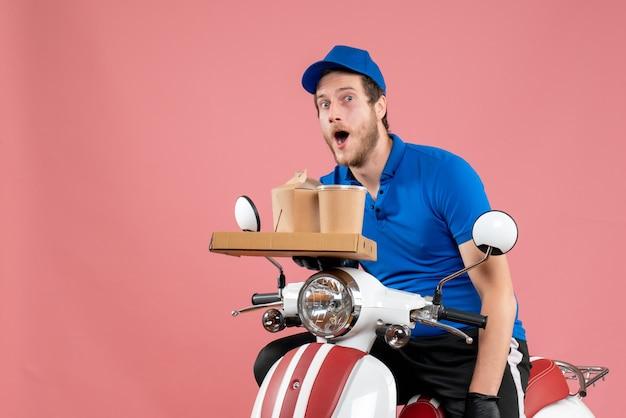 Vorderansicht männlicher kurier in blauer uniform mit kaffee- und lebensmittelbox auf dem rosafarbenen service-fast-food-arbeitslieferungsjob fahrradfarbe