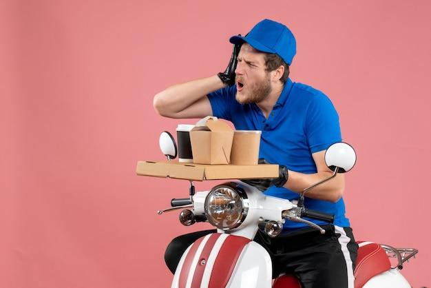 Vorderansicht männlicher kurier in blauer uniform mit kaffee- und lebensmittelbox auf rosafarbenem service-fast-food-arbeitsfahrradfarbe