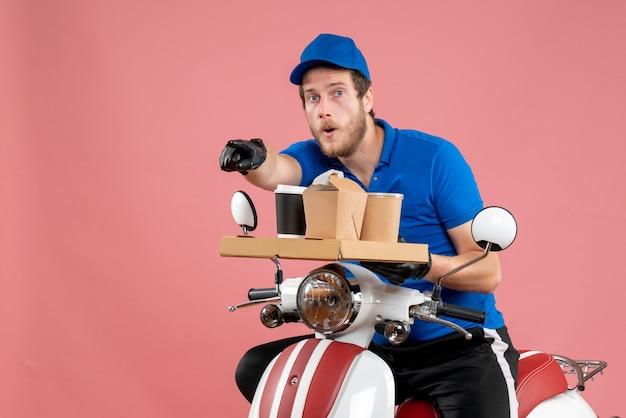 Vorderansicht männlicher kurier in blauer uniform mit kaffee- und lebensmittelbox auf rosafarbenem service fast-food-arbeitslieferungs-fahrradfarben