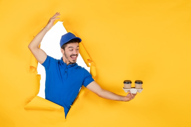 Vorderansicht männlicher kurier in blauer uniform mit kaffeetassen auf gelbem raum