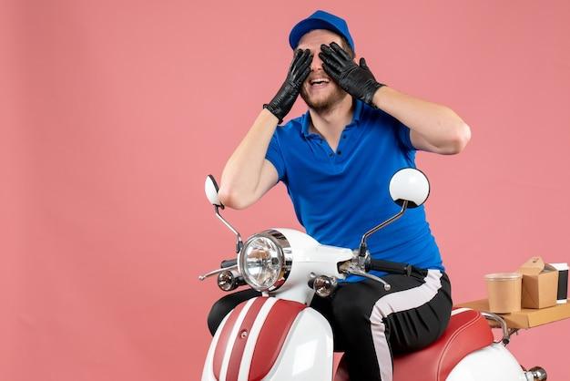 Vorderansicht männlicher kurier in blauer uniform und handschuhen auf der rosa farbe arbeiten fast-food-service-lebensmittel-job-lieferfahrrad
