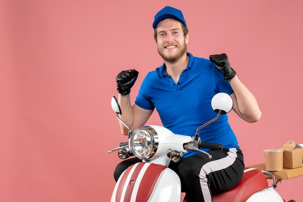 Vorderansicht männlicher kurier in blauer uniform und handschuhen auf rosafarbenem fast-food-service-lebensmittel-lieferfahrrad