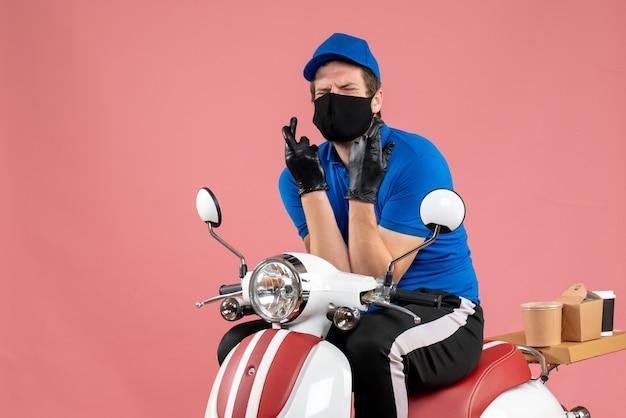 Vorderansicht männlicher kurier in blauer uniform und maske auf dem rosafarbenen liefervirus-lebensmittel-fast-food-service-fahrradarbeitscovid-job