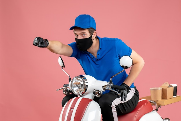 Vorderansicht männlicher kurier in blauer uniform und maske auf rosa lebensmitteljob arbeiten fast-food-lieferfahrradvirus covid