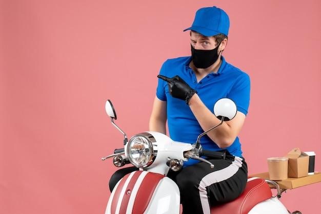 Vorderansicht männlicher kurier in blauer uniform und maske auf rosa lebensmitteljob arbeiten fast-food-service-liefervirus-kovid-