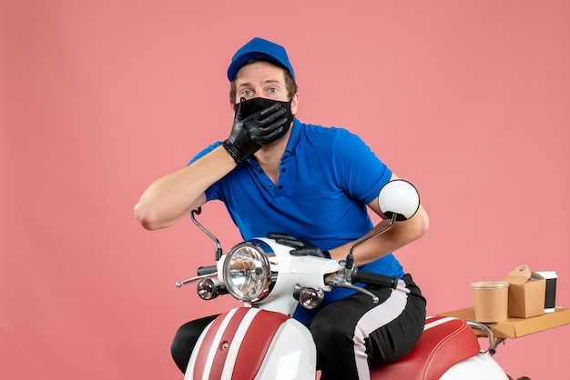 Vorderansicht männlicher kurier in blauer uniform und maske auf rosafarbenem fast-food-covid-lieferjob virus bike