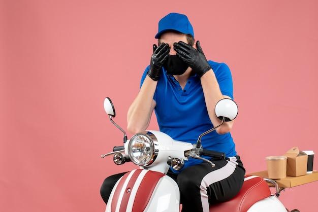 Vorderansicht männlicher kurier in blauer uniform und maske, die seine augen auf rosa virus-bike-job-lieferung, fast-food-covid-servicearbeiten schließt