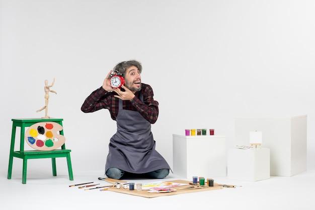 Vorderansicht männlicher maler im zimmer mit farben, die uhren auf weißem schreibtisch halten, kunstbildjob, farbmaler zeichnen
