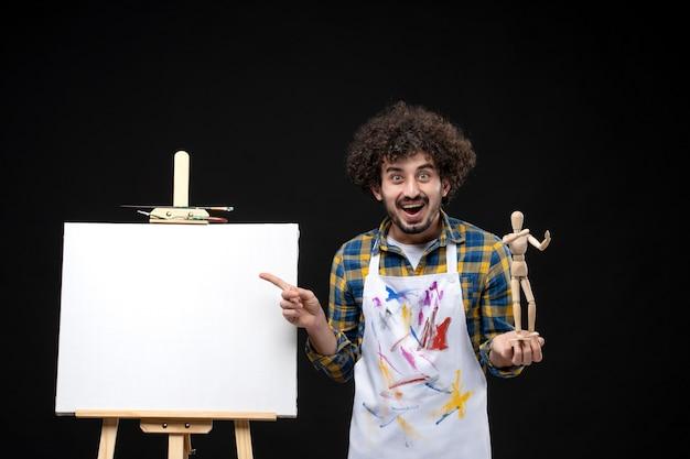 Vorderansicht männlicher maler mit staffelei, die menschliche spielzeugfigur an schwarzer wand hält