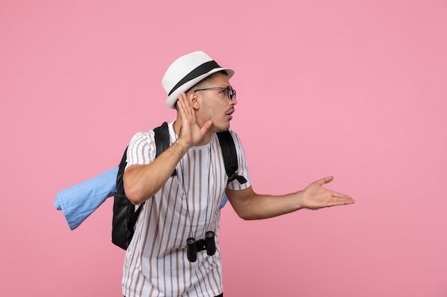 Vorderansicht männlicher tourist, der genau auf rosa wandgefühl-touristenfarbe hört