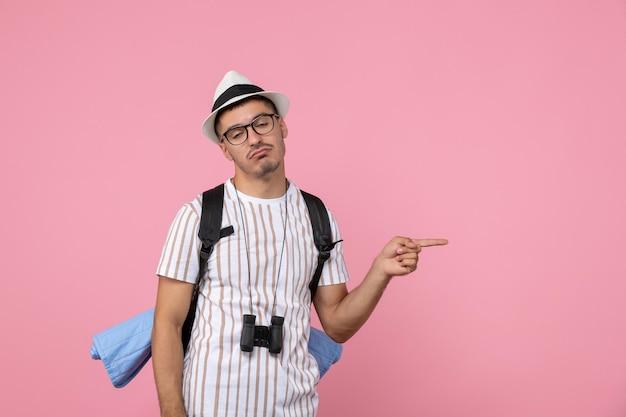 Vorderansicht männlicher tourist, der sich müde auf rosa wandemotionstouristenfarbe fühlt