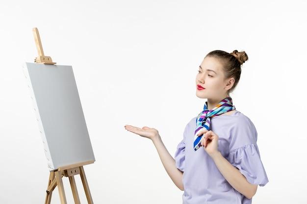 Vorderansicht malerin mit staffelei zum malen auf weißer wandkunst fotokünstler farbe zeichnen bildquaste