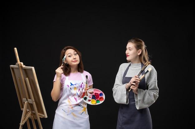 Vorderansicht malerin zeichnung auf staffelei mit anderen frauen auf einer schwarzen wand farbkünstler foto bild lackierung zeichnen kunst