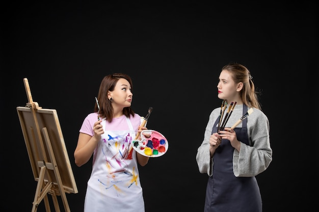 Vorderansicht malerinnen, die farben und quasten zum zeichnen auf der schwarzen wand halten bildkunst farbkünstler fotojob zeichnen malerei