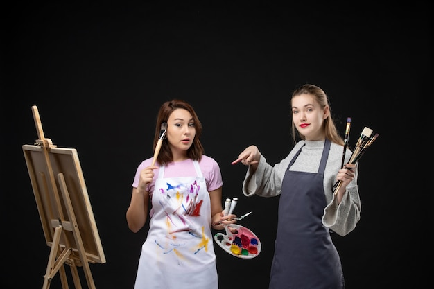 Vorderansicht malerinnen, die farben und quasten zum zeichnen auf schwarzer wand halten, zeichnen malerei-job-bild-kunst-foto-farben-künstler