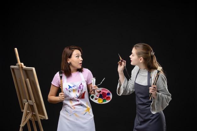 Vorderansicht malerinnen mit farben und quasten zum zeichnen auf der schwarzen wandmalerei farbe zeichnen job bildkunst fotokünstler