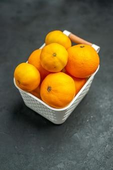 Vorderansicht mandarinen und orangen im plastikkorb auf dunklem freiraum