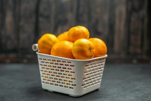 Vorderansicht mandarinen und orangen im plastikkorb auf dunklem freiraum Kostenlose Fotos
