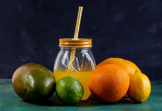 Vorderansicht mango mit zitronen-limetten-orange und saft in einem glas mit einem gelben strohhalm
