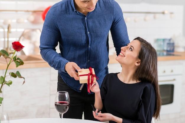 Vorderansicht mann, der seiner frau ein valentinstaggeschenk gibt