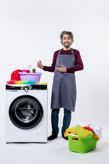 Vorderansicht-mann in schürze, der in der nähe einer waschmaschine an einer weißen wand steht