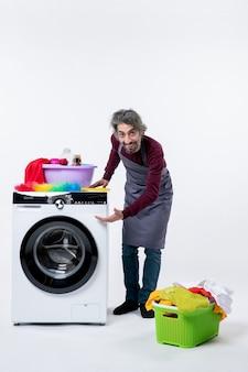 Vorderansicht mann in schürze steht in der nähe einer waschmaschine auf weiß isolierter wand