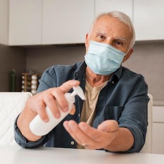 Vorderansicht mann mit maske und desinfektionsmittel