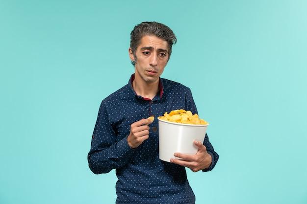 Vorderansicht mann mittleren alters, der cips isst und auf blauer oberfläche betont