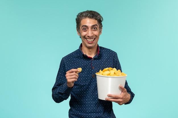 Vorderansicht mann mittleren alters, der cips isst und auf blauer oberfläche lacht