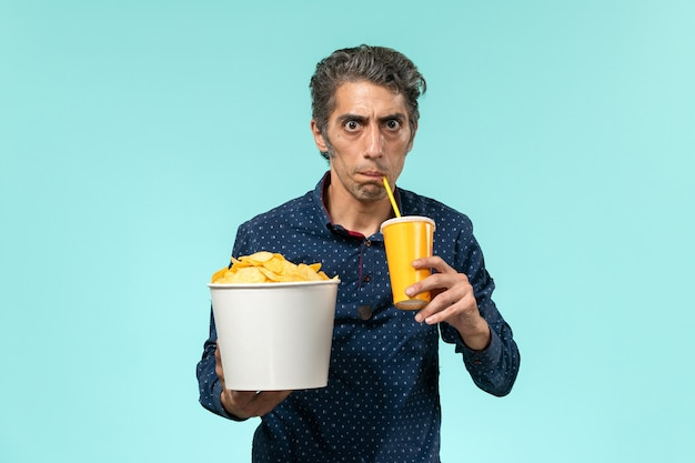 Vorderansicht mann mittleren alters, der kartoffelspitzen hält und soda auf einer blauen oberfläche trinkt