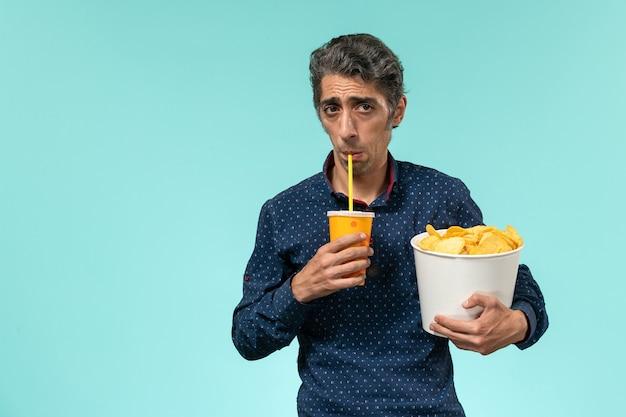 Vorderansicht mann mittleren alters, der kartoffelspitzen und soda auf einem hellblauen schreibtisch hält
