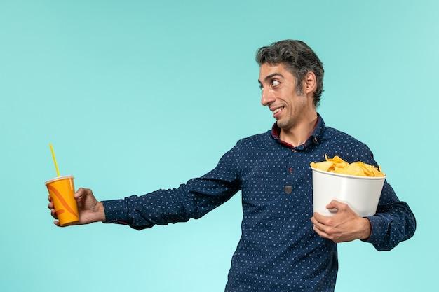 Vorderansicht mann mittleren alters, der kartoffelspitzen und soda auf hellblauer oberfläche hält
